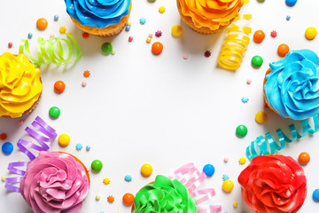 Flat lay composition with colorful birthday cupcakes on light background