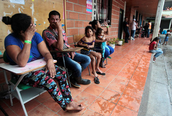 People rest in school used as a shelter after the Colombian government ordered the evacuation of residents living along the Cauca river