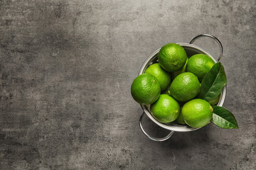 Colander with fresh ripe limes on gray background, top view