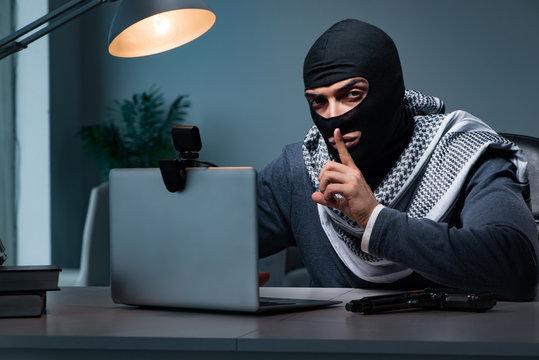 Hacker wearing balaclava mask hacking computer