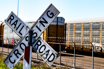 Old worn railroad crossing sign in front of a barbed wire fence and cars