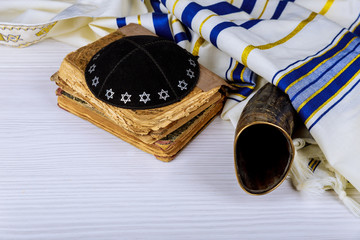 The Hebrew handwritten Torah, shofar ram's horn on a synagogue alter, with Kippah and Talith