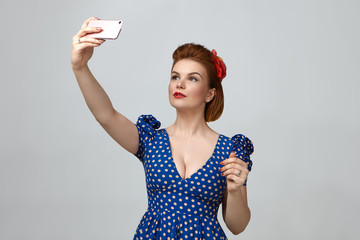 Waist up portrait of gorgeous fashionable young lady dressed like 1950s pin up girl holding smart phone above her and taking selfie while posting pictures via social networks, having confident look