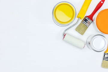 painting tools for house renovation. paint cans, roller and brushes on white wooden background
