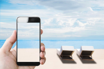 Summer holiday, hand holding mobile smartphone on the beach in summer