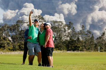 People pose for a photo as ash erupts from the Halemaumau Crater near the community of Volcano