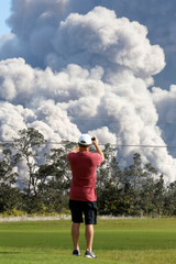 A man takes a photo as ash erupts from the Halemaumau Crater near the community of Volcano