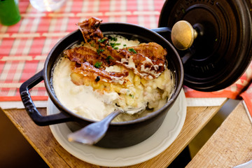 Delicious traditional alsacian pasta plate Spatzle, with bacon and served on a black pan