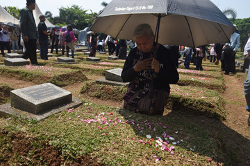 Maria Sanu, the mother of 16-year-old Stevanus Sanu, who died during the May 1998 riots, prays at a mass grave for victims of the tragedy during a 20th anniversary commemoration at Pondok Ranggon in Jakarta