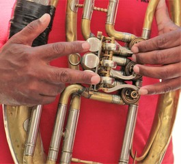 hands on a brass instrument,musicians playing outdoor,close up