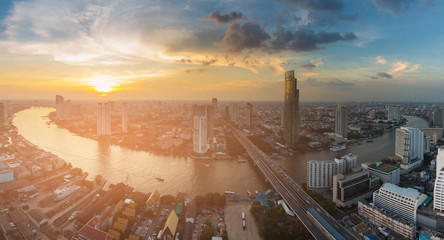 Sunset skyline over river curved Bangkok city business downtown, cityscape background, Thailand