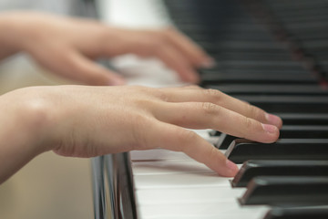 children's hands are playing the piano. Child's hand on piano keys.