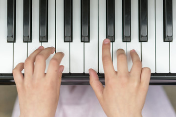 Hands on piano keys close-up. Closeup girl's hand playing piano. Favorite classical music. Top view with dark vignette. View from above