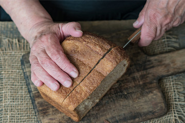 Old woman's hands, grandmother's hands with rye bread close-up, concept of time, life