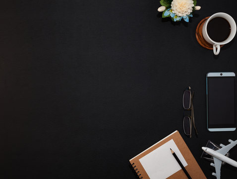 Black leather office table with paper note,smartphone, office supplies and coffee cup, Top view with copy space.