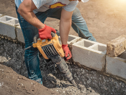 Worker with a jackhammer, foundation, building blocks.
