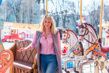 Nice beautiful fashionable woman in an amusement park. Pretty , middle age lady having fun at an amusement park. Joy in adult life
