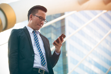 Modern young businessman wear black suit hand holding smartphone. Professional business man standing outside office and looking mobile phone with a serious facial expression. with copy space