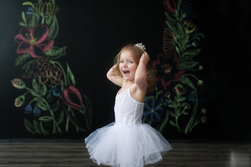 Cute little ballerina in white ballet costume is dancing in the room. Kid in dance class.
