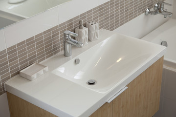 modern style faucet mixer on a white sink in a beautiful gray and white bathroom