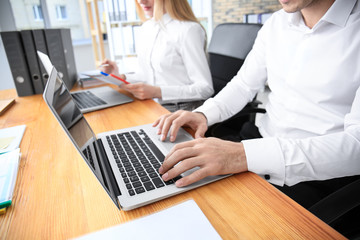 Young employees working with laptops in office