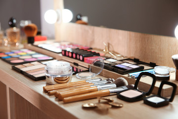 Cosmetic and tools of professional makeup artist on table indoors