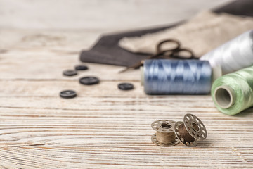 Composition with threads and sewing accessories on wooden background