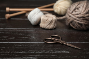 Composition with threads and knitting accessories on wooden background