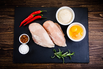 Raw chicken fillet on wooden table