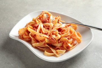 Plate with delicious pasta bolognese on grey background