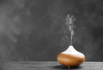 Aroma oil diffuser on table against grey background. Air freshener Fototapete