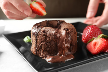 Chef decorating delicious fresh chocolate fondant with strawberry at table. Lava cake recipe