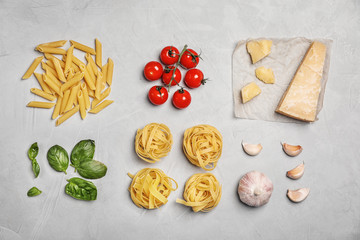 Flat lay composition with uncooked pasta and products on grey table