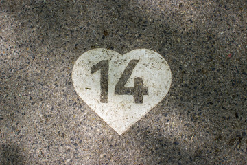 Digit 14 painted in white heart on a pavement.