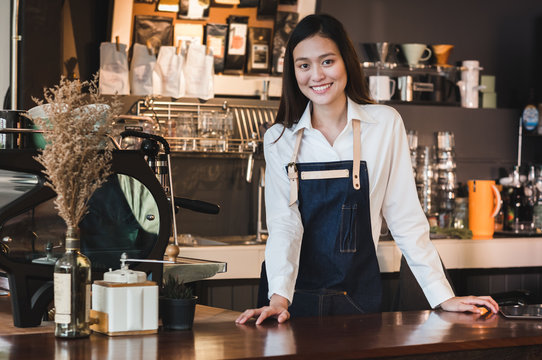 Asian female barista wear jean apron place her hand on counter bar and smiling to customer,cafe service concept,owner business start up