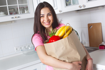 Young healthy woman with fresh vegetables on the kitchen