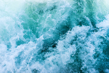Turquoise blue wavy seawater with foam and waves, background texture.