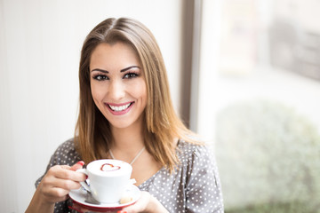 Happy woman holding a cup of coffee
