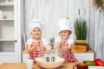 Two little girls baby twin sisters in the kitchen bake cookies from flour.