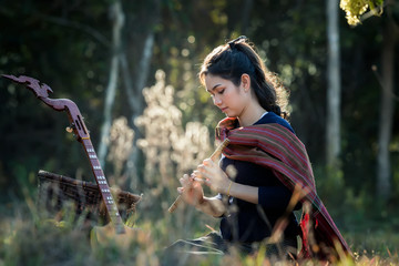 Asia women are playing on the flutes, sitting in a forest at countryside.
