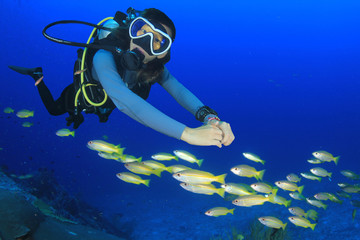 Young female scuba diver underwater with fish