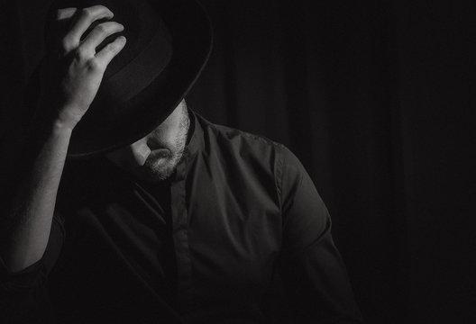 man beard black hat bends head