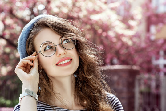 Outdoor close up portrait of young beautiful happy smiling girl wearing round transparent glasses, blue beret. Model looking up, posing in street. Spring fashion concept. Copy, empty space for text