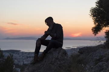 Silhouette eines bärtigen Mannes der bei Sonnenuntergang auf einem Felsen sitzt