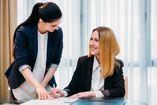 secretary job. professional duties. young employee assisting her boss in signing documents. good working relationships and comfortable office workspace