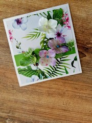 Vivid greeting card with tropic print on a wooden background close-up