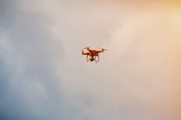 Red quadrocopter flying in the cloudy sky with sunlight warm efffect