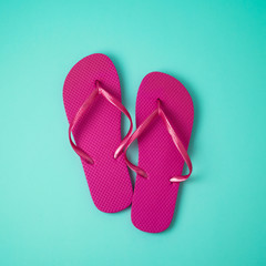 Pink flip flops over blue background.