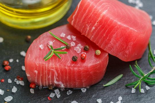 Raw Tuna fish steaks with sea salt, pepper and rosemary