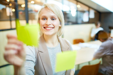 Happy businesswoman with toothy smile making note on one of reminders while working in office